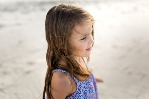 A young girl at the beach watching the ocean