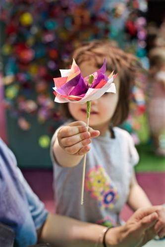 A young girl / child holds up a paper flower she has made