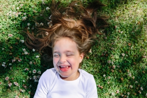 A young girl lying in a field laughing