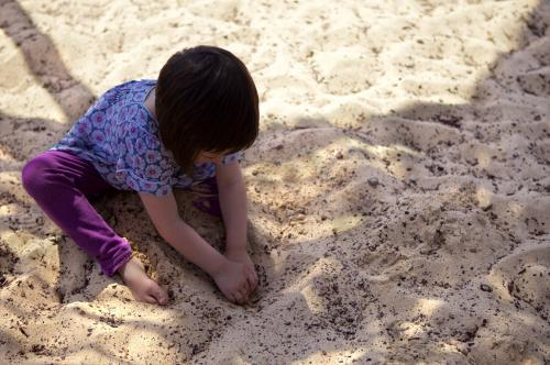 A young girl playing in the sand, digging for treasure in a sandpit