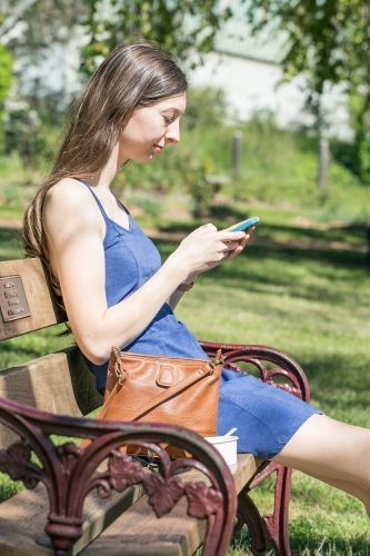 A young woman with long hair sits on a park bench looking at her phone