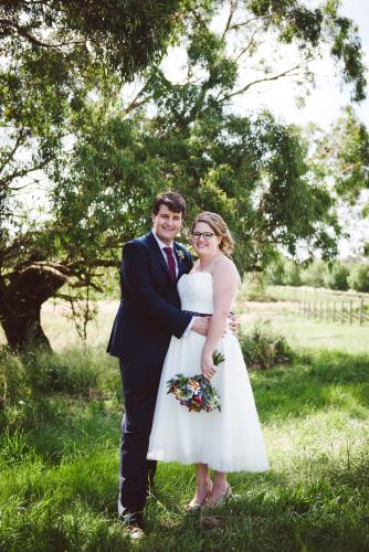 Bride and Groom standing beside a tree in paddock looking at camera