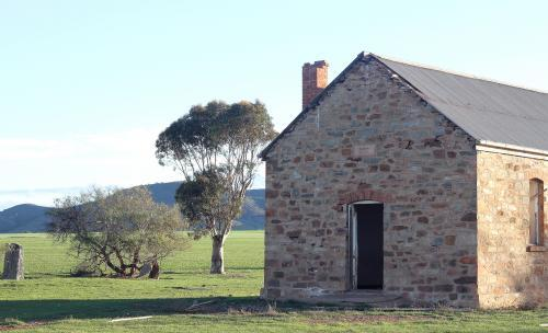 Abandoned brick building in a green paddock