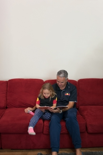 Aboriginal father and daughter reading on lounge