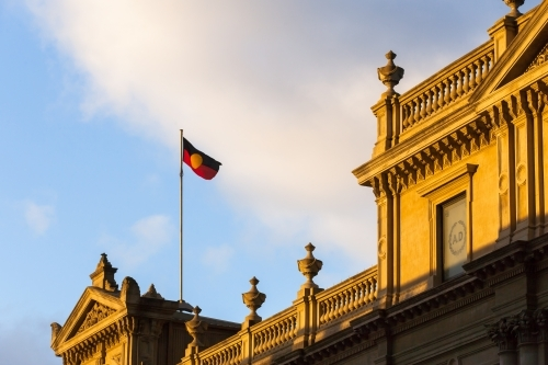 aboriginal flag flying above a heritage buildings