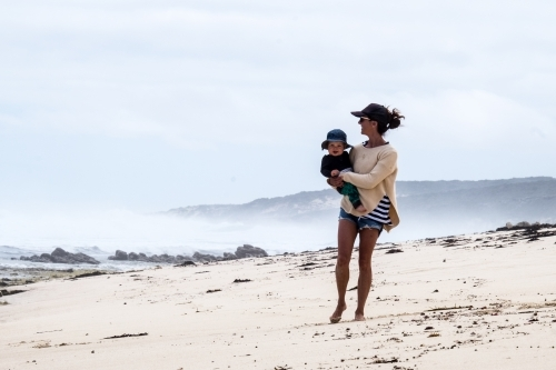 Active Mother carrying baby boy along remote coastline