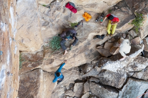 Aerial of four male rock climbers at the bottom of a crag
