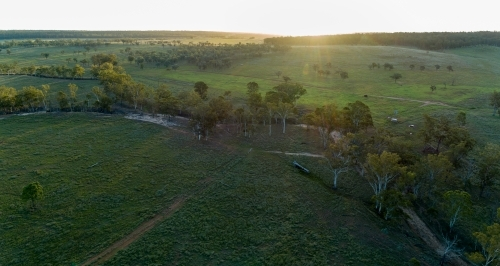 Aerial panorama of a farm creek at dusk.