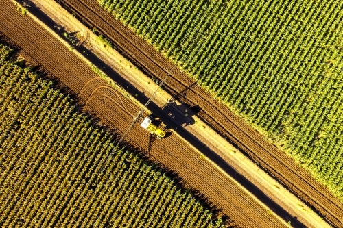 Aerial view of a boom sprayer turning between crops of sorghum