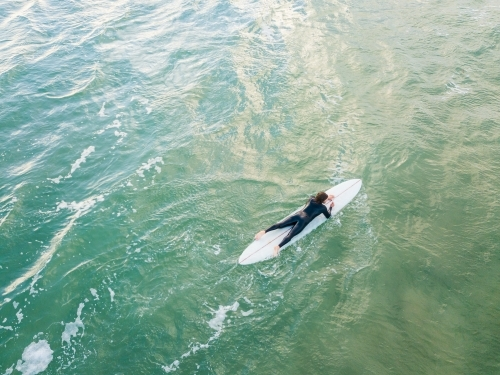 Aerial view of a lone surfer paddling a board on the ocean