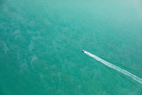 aerial view of boat heading out in blue green sea