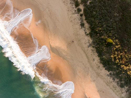 Aerial view of breaking wave washing on a sandy Beach