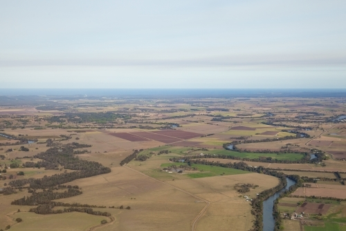 Aerial view of river winding through farm land in the country
