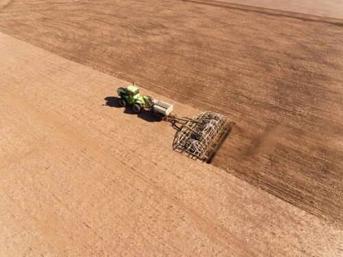 Aerial view of tractor and seeding bar planting crop