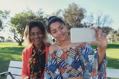 African mother and multicultural teen daughter taking selfie
