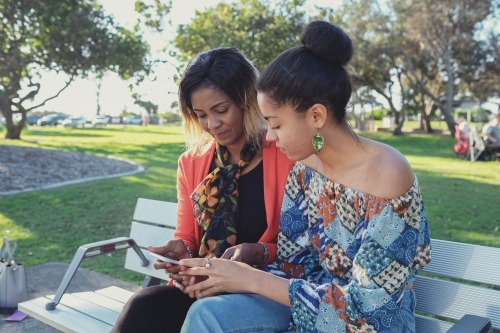 African mother and multicultural teen daughter using mobile phone