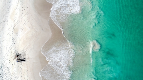An aerial shot of a fisherman trying his luck in the ocean