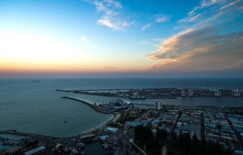 An aerial view of a port city at sunset