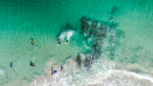 An aerial view of bodyboarders paddling for position