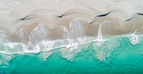 An aerial view of water swirling on the shore