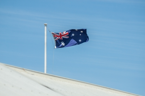 An Australian flag flying over a tin roof