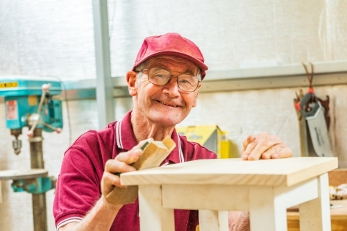 An elderly handyman smiling over the top of a piece of woodwork.