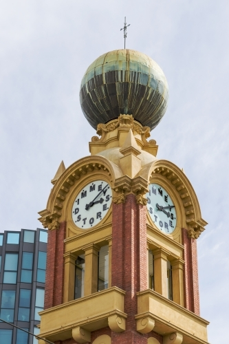 An ornate historic clock tower with a large copper dome on top.