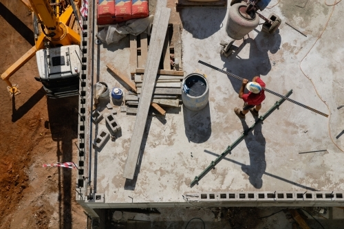 An overhead view of a construction worker carrying a beam on a building site