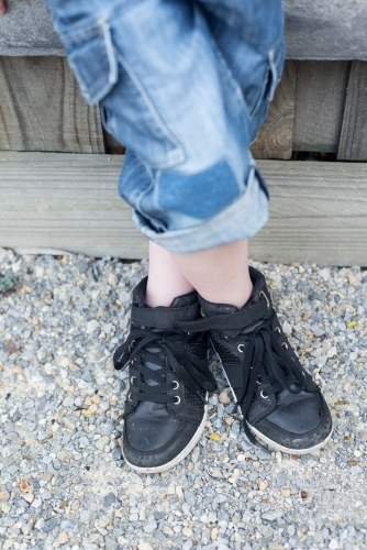 Anonymous child wearing jeans leaning against a wooden fence