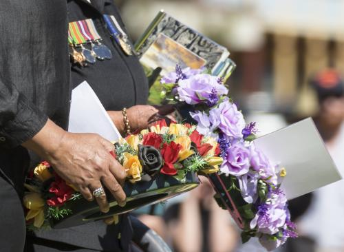 Detail of two people carrying a wreath on ANZAC Day