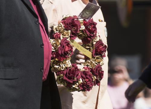 Detail of two people carrying a wreath with red and gold flowers on ANZAC Day