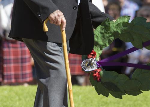 Detail of elderly male digger laying a wreath on ANZAC Day