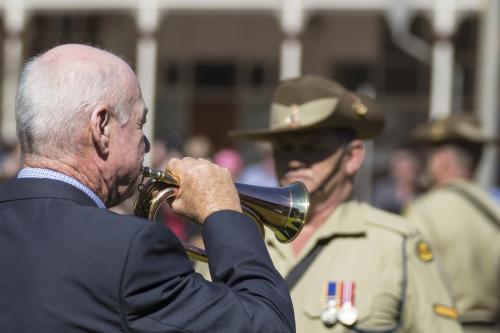 A bugle player on ANZAC Day with soldiers in uniform