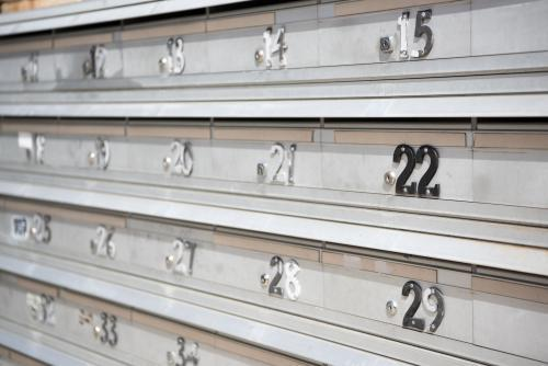 apartment block aluminium mailboxes with worn numbers
