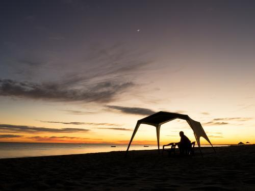 Man and tent silhouetted against sunset on a beach