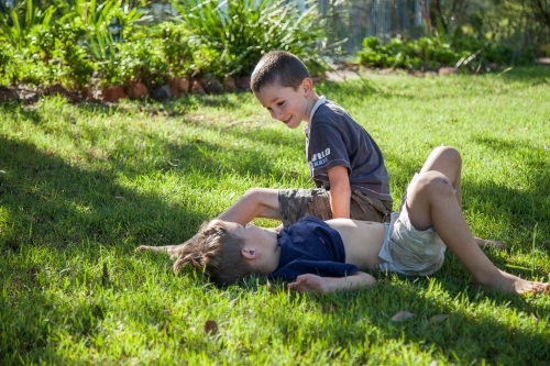 Two brothers tackling on the grass outside