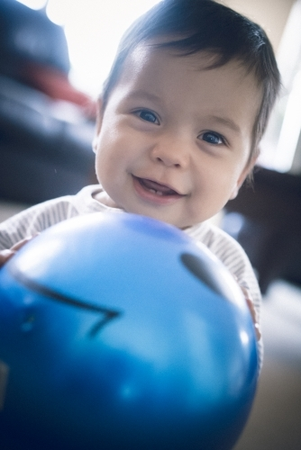 Cute 1 year old mixed race boy plays at home with a smiley face ball