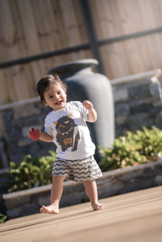 Cute 1 year old boy takes his first steps outside in his suburban backyard