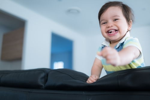 Cute mixed race toddler plays on a black leather lounge at home