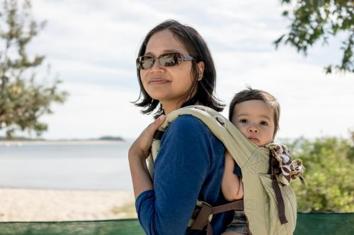 Asian mum outside at the beach walking in the summer sun with her mixed race baby boy