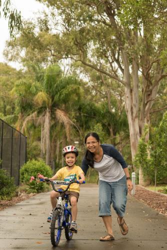 Asian mum teaching her mixed race boy to ride a bike
