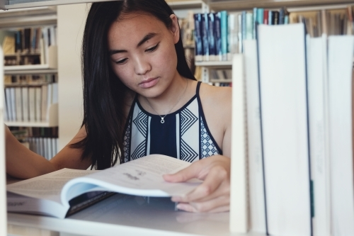 Asian student reading book in university library