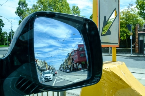 View of urban street in car wing mirror