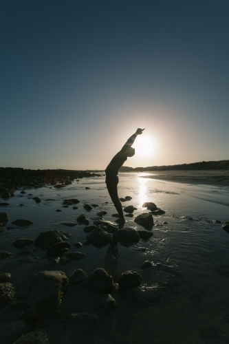 Silouette of man doing yoga poses on beach at sunset