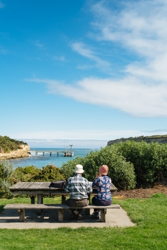 Two seniors sitting at picnic table on Great Ocean Road
