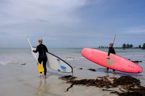 Two girls carrying SUP into ocean