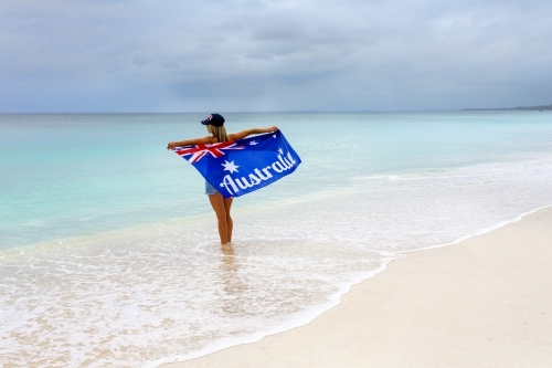 Aussie culture. A woman stands on a stunning beach holding proudly the Australian Flag