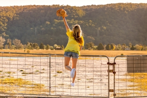 Aussie woman standing on a rural farm gate with one arm raised holding hat