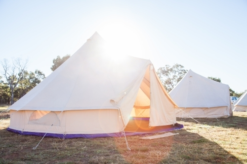 Sun flare over huge white tent with open flaps in the morning