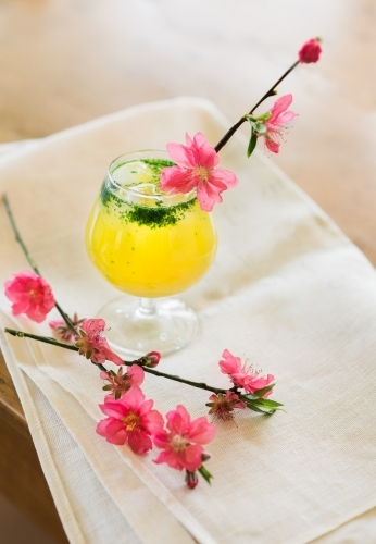 Pink cherry blossoms and cocktail with napkin